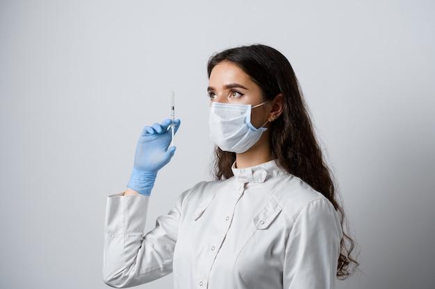 Medico che tiene la siringa con il vaccino contro il coronavirus. ragazza attraente in guanti medicali con siringa e farmaci