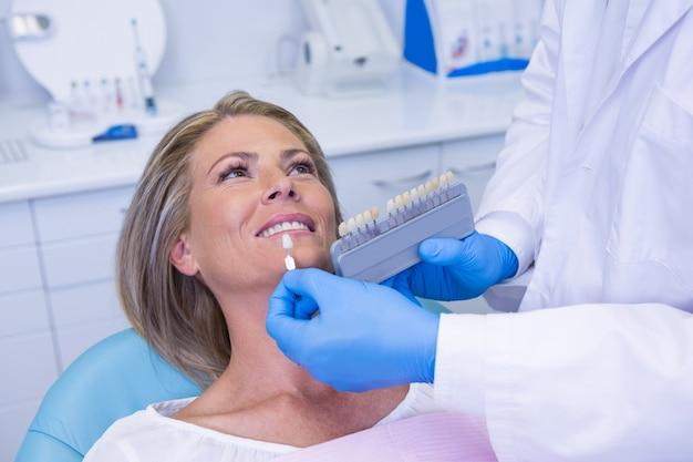 Medico che tiene apparecchiature per lo sbiancamento dei denti dal paziente