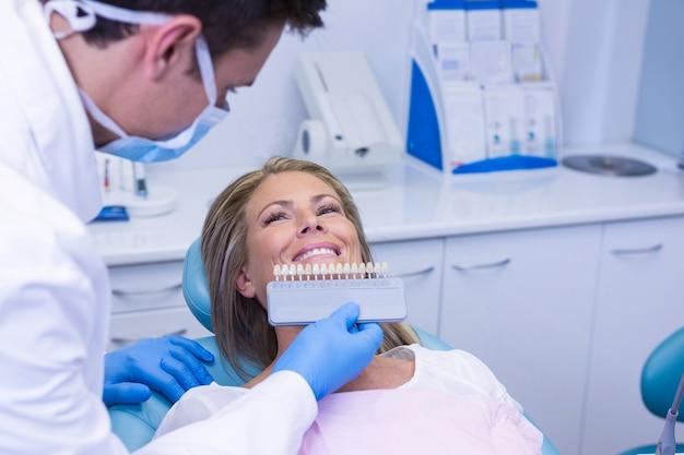Medico che tiene apparecchiature per lo sbiancamento dei denti dal paziente sorridente