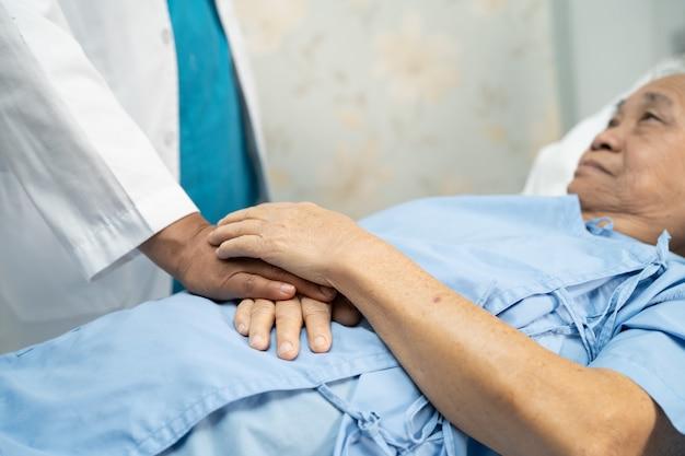 Medico che tiene le mani toccanti asian senior o anziana signora anziana paziente con amore, cura, aiuto, incoraggiamento ed empatia nel reparto ospedaliero di cura, concetto medico sano e forte