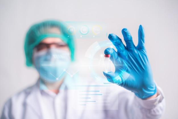 Medico che tiene in mano una bottiglia di vaccino con moderna interfaccia hud su sfondo ospedaliero, innovazione e tecnologia medica.