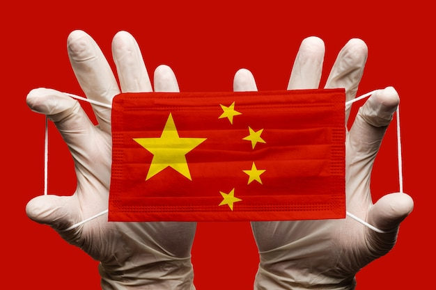 Medico che tiene in guanti bianchi una maschera medica per la protezione del viso, bendaggio respiratorio con bandiera nazionale cinese sovrapposta alla maschera. concetto su sfondo rosso, impatto globale del coronavirus covid-19