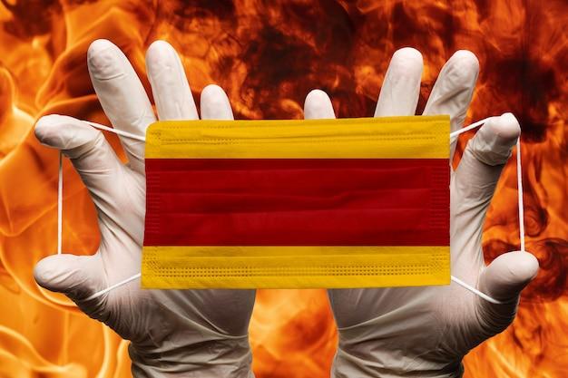 Medico che tiene in guanti bianchi maschera medica per la protezione del viso, bendaggio respiratorio con bandiera nazionale spagnola sovrapposta alla maschera. concetto su sfondo di pericolose fiamme rosse fuoco naturale
