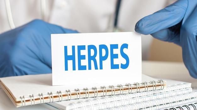 Medico in possesso di una carta di carta bianca con il testo: herpes. concettuale sanitario per ospedali, cliniche e aziende mediche.