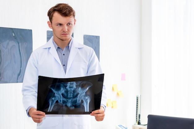 Medico che tiene i raggi x nella stanza hopital
