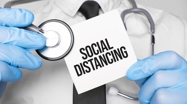 Stetoscopio medico con stetoscopio e foglio di carta con testo social distance