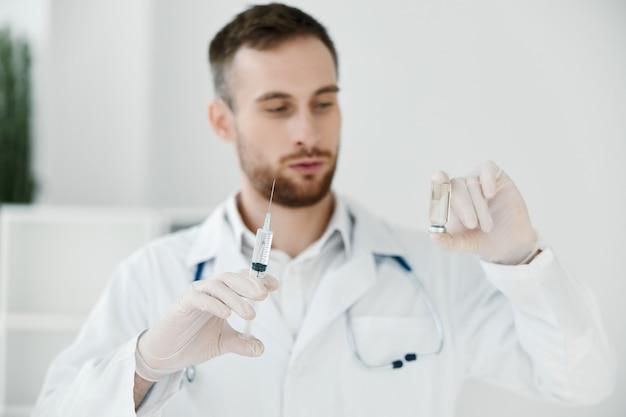 Il medico tiene in mano una fiala con un vaccino, un camice medico e guanti protettivi
