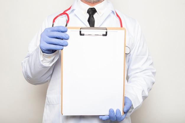 Il medico tiene una lavagna per appunti con uno spazio vuoto per il testo