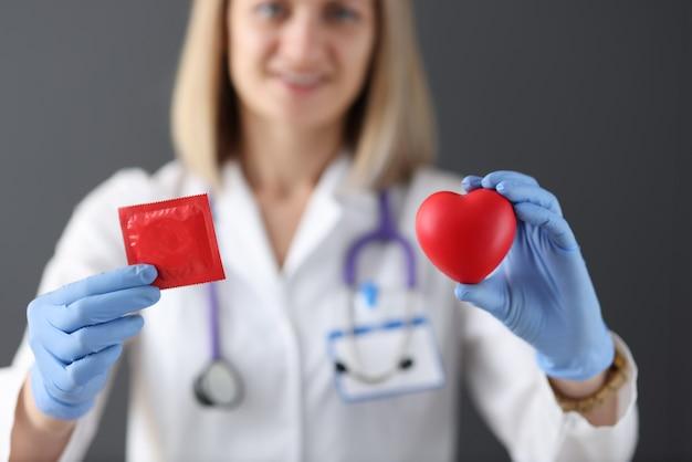 Il dottore tiene in mano il preservativo e il cuore. concetto di rapporto sessuale sano