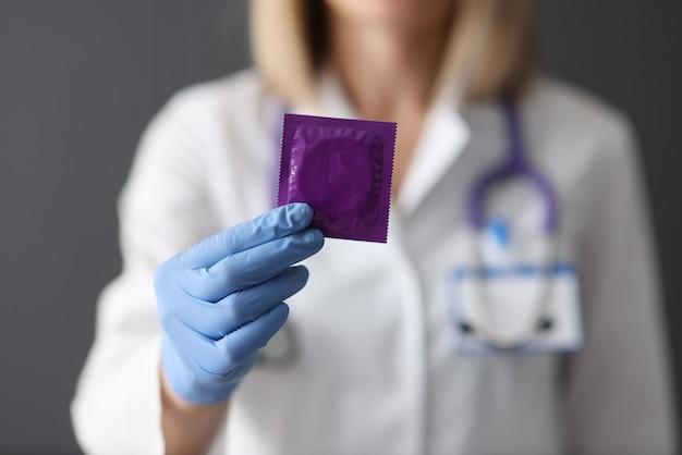 Il dottore tiene il preservativo nella sua sicurezza della mano durante il concetto di rapporto