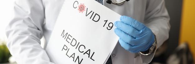 Il medico tiene il documento con l'iscrizione pianificazione medica per il coronavirus.