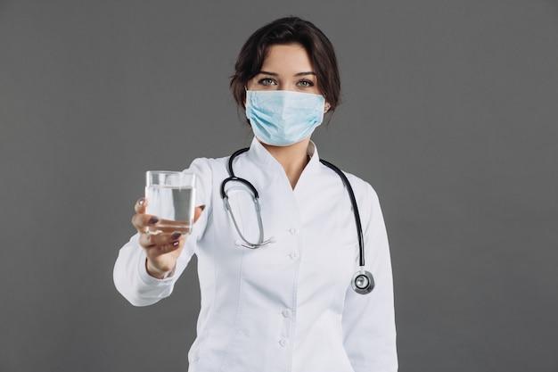 Il medico tiene un bicchiere d'acqua e raccomanda di bere acqua per combattere il coronavirus 2019-ncov
