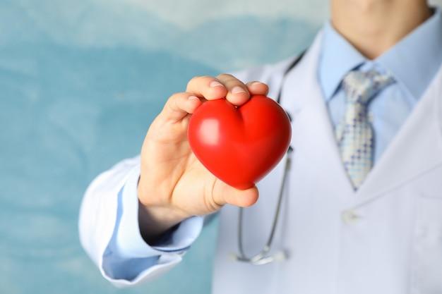 Medico tiene il cuore contro la superficie blu, da vicino