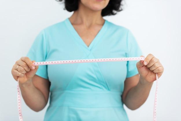 Il medico tiene tra le mani un centimetro per misurare la circonferenza dell'addome ostetricia