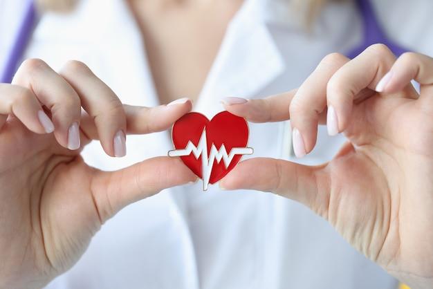 Il medico tiene tra le mani un'icona con il cardiogramma del cuore. cuore e concetto di malattia vascolare