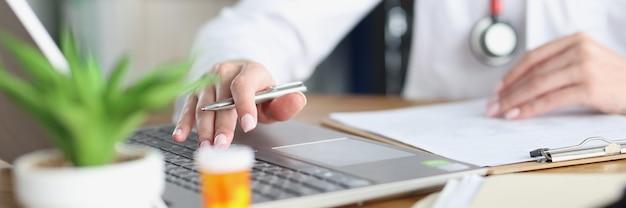 Il dottore tiene la penna e lavora al computer portatile in studio medico