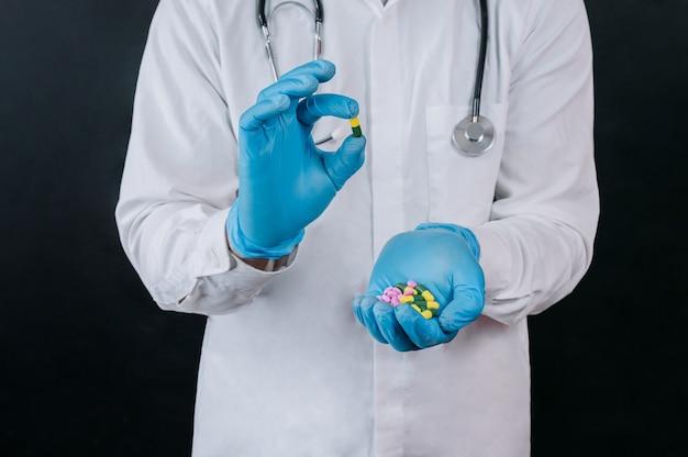 Il medico tiene le pillole nelle sue mani su uno sfondo scuro.