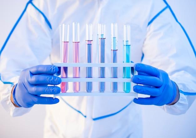 Il medico tiene le provette con vaccini varianti delta del coronavirus epidemiologo che tiene il rilevamento del test di