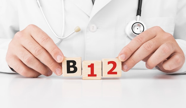 Il medico tiene i cubi di legno nelle sue mani con il testo b12