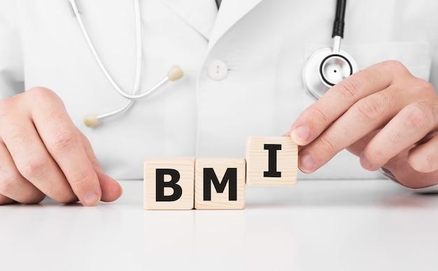 Il medico tiene i cubi di legno nelle sue mani con il testo bmi