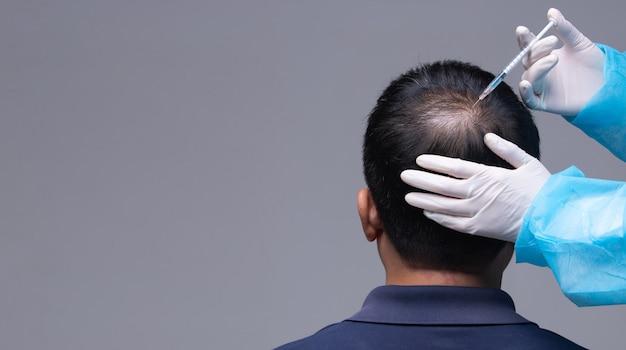 Il medico inietta il trattamento delle vitamine del siero caduta dei capelli Foto Premium