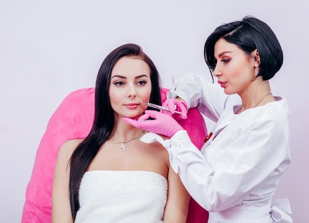 Medico che inietta in un bel viso di una giovane donna. concetto di chirurgia plastica.