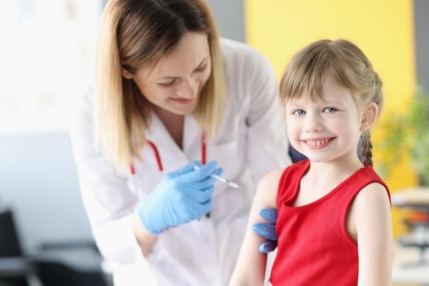 Medico che inietta la medicina nella spalla della bambina in clinica