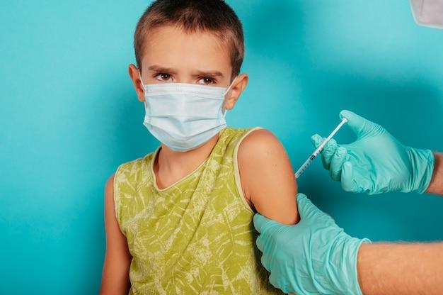 Il medico inietta il vaccino a un bambino contro il covid coronavirus