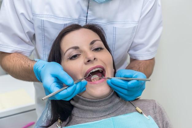 Medico che ispeziona i denti dei pazienti con la fine dello specchio