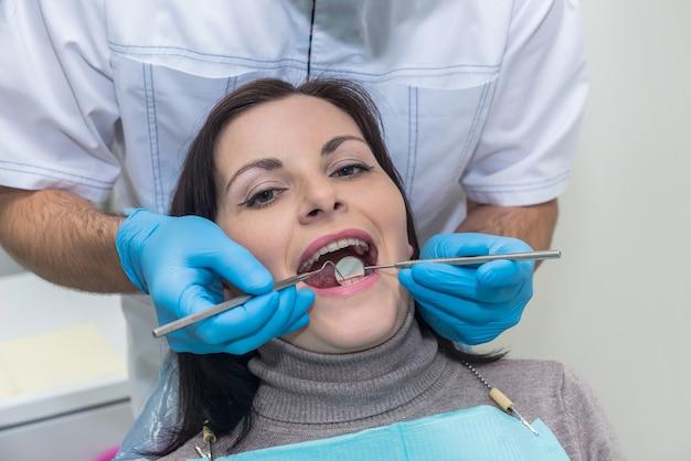 Medico che ispeziona i denti dei pazienti con lo specchio si chiuda