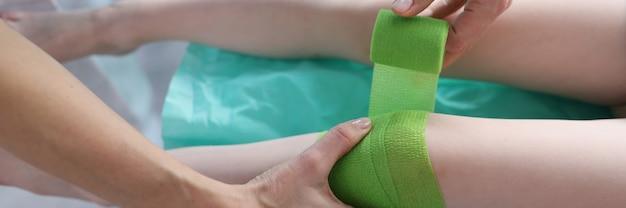 Il dottore sta fasciando la gamba dolorante del bambino con una benda verde in primo piano della clinica