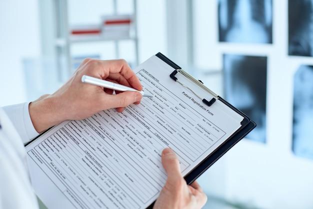 Il medico sta compilando il modulo di registrazione dei pazienti.