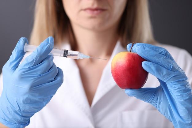Il medico sta tenendo la siringa con l'ago e una mela. tipi di mesoterapia per il concetto di ringiovanimento
