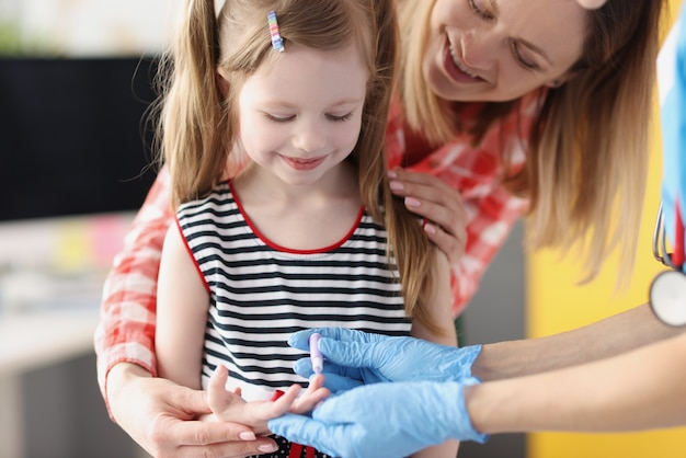 Assistente di laboratorio medico che preleva il sangue della bambina usando la lancetta in clinica