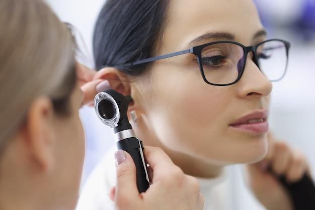 Medico laringologo che esamina l'orecchio di una paziente con gli occhiali usando l'otoscopio