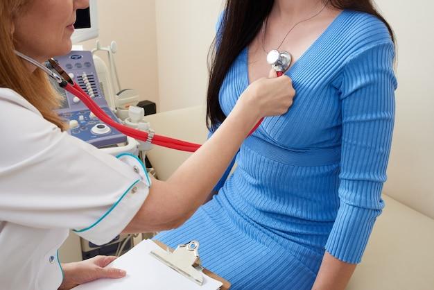 Stetoscopio d'ascolto del medico con al cuore della giovane paziente femminile