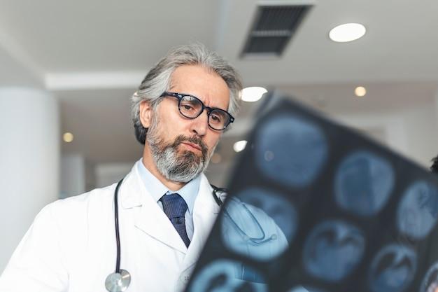 Medico che osserva la pellicola dei raggi x del paziente di polmonite per diagnosticare l'enfisema, polmone infiammato.