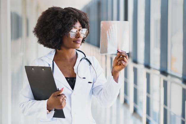 Medico che osserva la pellicola dei raggi x della spalla in ospedale. concetto di radiografia. medico femminile di radiologia esaminando la pellicola a raggi x del paziente nella stanza d'ospedale. Foto Premium