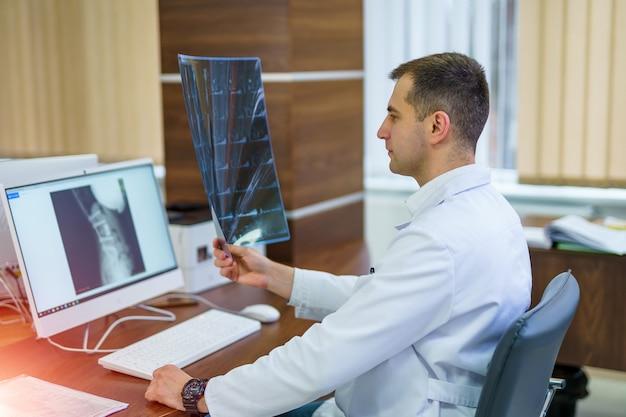 Il medico esamina una radiografia e controlla la diagnosi.