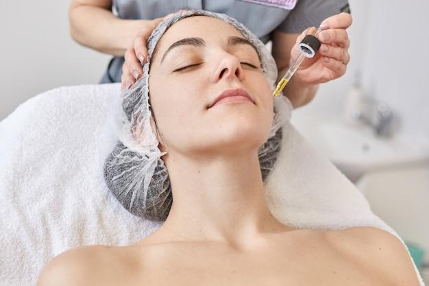 Il medico esegue la procedura di estetista, applica il siero vitaminico sul viso della bella donna, cliente della clinica di cosmetologia. la giovane femmina vuole migliorare il suo aspetto con la medicina etetica. concetto di cura della pelle