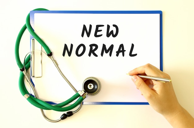 Il medico fa la scritta new normal nel documento. cartella e stetoscopio