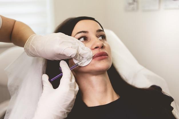 Il medico fa l'iniezione paziente di botox sulle labbra.