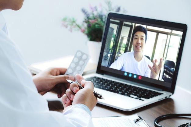 Medico che effettua una videochiamata e consiglia pillole o farmaci a un paziente maschio malsano in clinica