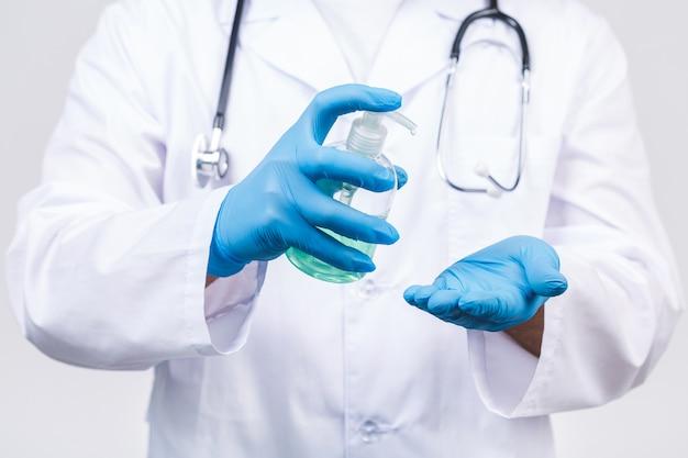 Aggiusti l'uomo nei guanti della maschera di protezione dell'abito isolati. epidemia di pandemia coronavirus 2019-ncov sars covid-19 virus dell'influenza. bottiglia con alcool disinfettante liquido antibatterico.
