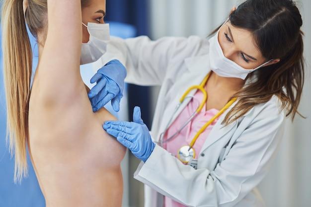 Dottore in maschera che controlla il seno al suo paziente