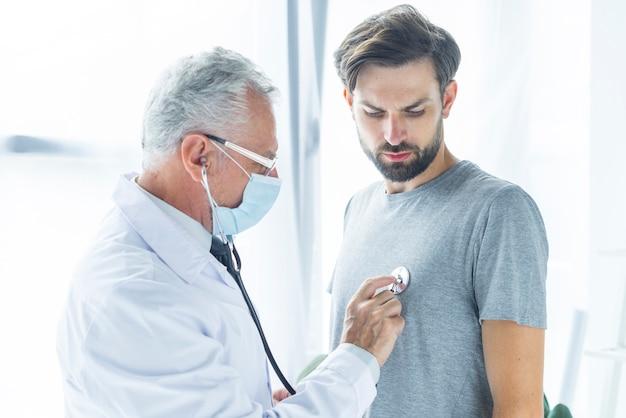 Medico in maschera che esamina uomo barbuto