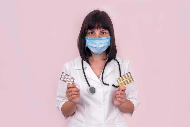 Dottore in maschera che mostra le pillole in blister