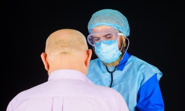 Medico in maschera con lo stetoscopio che controlla paziente. uomo malato in ospedale. coronavirus. assistenza sanitaria.
