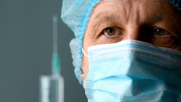 Il dottore in maschera con la siringa si sta preparando per l'iniezione