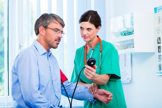 Medico che misura la pressione sanguigna sul paziente